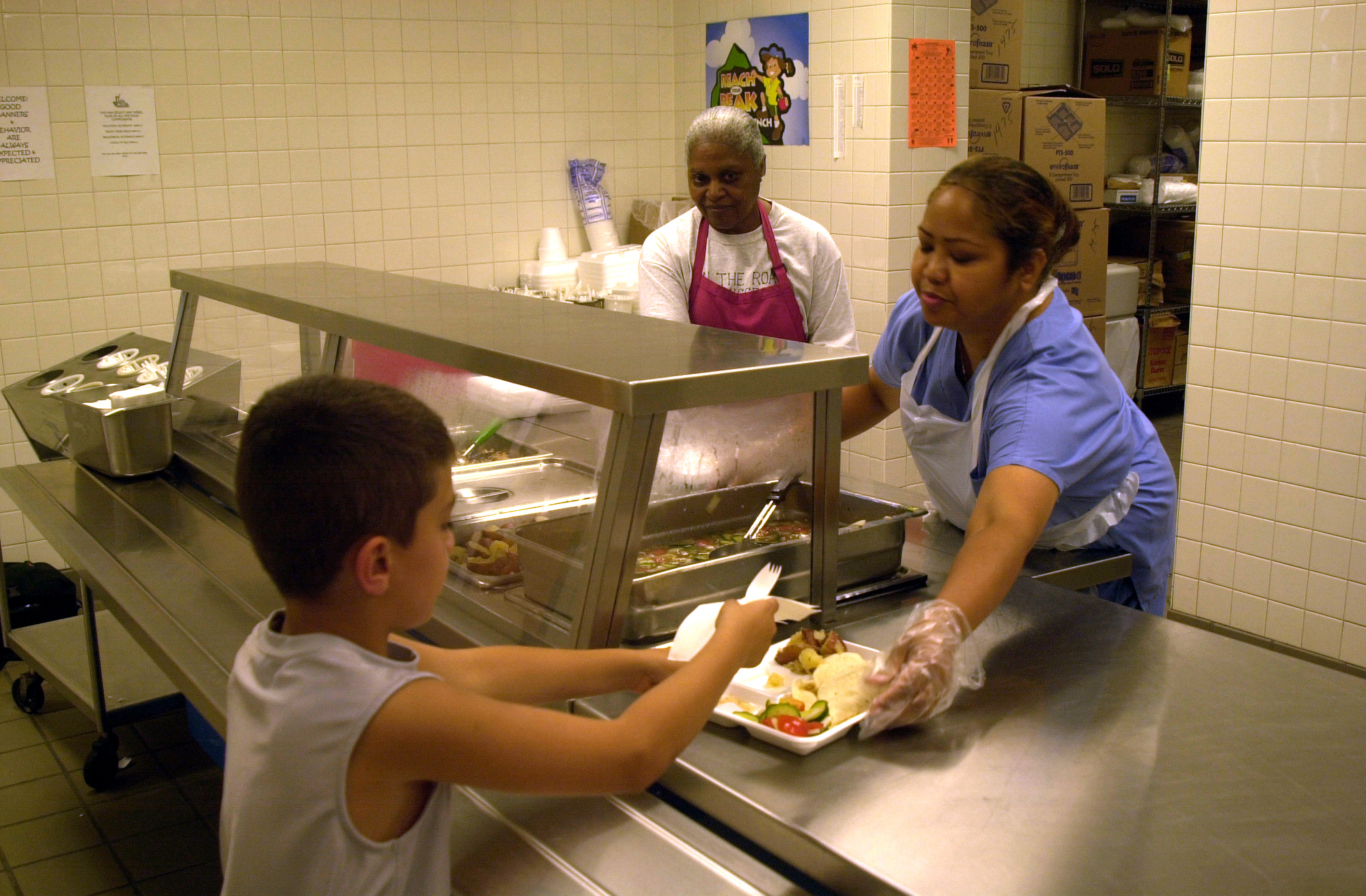 MARINE CORPS BASE CAMP LEJEUNE, N.C. – Aurora Paltt a cafeteria worker at Tarawa Terrance II Elementary School serves a child a lunch here July 11. Preschoolers to 18-year-olds can get a free lunch from Department of Defense Dependent Schools at Tarawa Terrance II Elementary School and Brewster Middle School. (Official U.S. Marine Corps photo by Lance Cpl. Brandon R. Holgersen)
